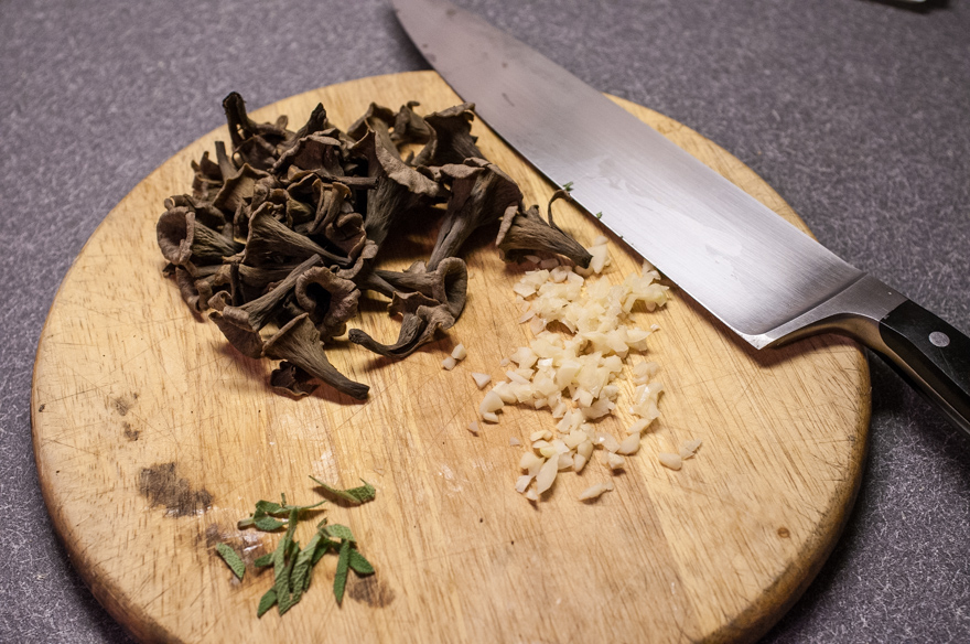Black trumpet mushrooms on cutting board with garlic, sage, and chef's knife